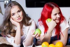 Deux jeunes filles dans la cuisine parlant et mangeant Image libre de droits