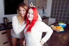 Deux jeunes filles dans la cuisine parlant et mangeant Photographie stock