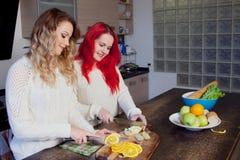 Deux jeunes filles dans la cuisine parlant et mangeant Photo libre de droits