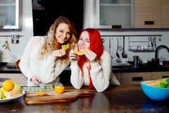 Deux jeunes filles dans la cuisine parlant et mangeant du fruit, mode de vie sain Photo libre de droits
