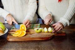 Deux jeunes filles dans la cuisine parlant et mangeant du fruit, mode de vie sain, plan rapproché Image stock