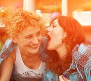 Deux jeunes filles dans le plaid détendent et socialisent l'appel, message, vont Photographie stock libre de droits