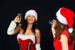 Deux jeunes filles dans les robes et des chapeaux rouges Santa& x27 de Noël ; s photographié sur un fond foncé Photographie stock libre de droits