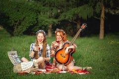 Deux jeunes filles de hippie ayant l'amusement sur le pique-nique Image stock