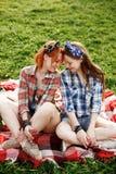 Deux jeunes filles de hippie ayant l'amusement sur le pique-nique Images libres de droits