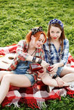 Deux jeunes filles de hippie ayant l'amusement sur le pique-nique Images stock