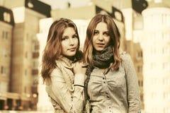 Deux jeunes filles de mode marchant dans une rue de ville Photos stock