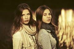 Deux jeunes filles de mode marchant par le lac Photos stock