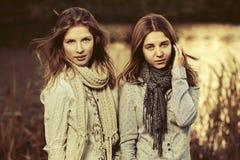 Deux jeunes filles de mode marchant par le lac Photos libres de droits