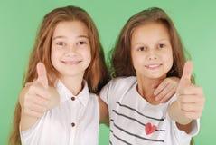 Deux jeunes filles de sourire d'école montrant des pouces  Photo stock