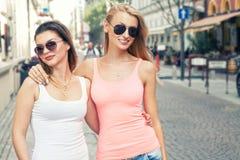 Deux jeunes filles de sourire marchant dans la ville Image libre de droits