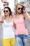 Deux jeunes filles de sourire marchant dans la ville Images stock