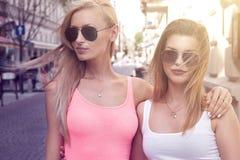 Deux jeunes filles de sourire marchant dans la ville Photographie stock libre de droits