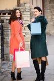 Deux jeunes filles descendent la rue tout en faisant des emplettes Images libres de droits