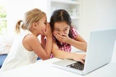 Deux jeunes filles employant l'ordinateur portable à la maison et le chuchotement Photographie stock libre de droits