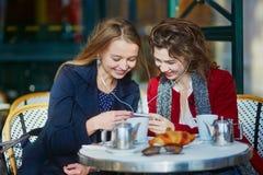 Deux jeunes filles en café extérieur parisien Photographie stock