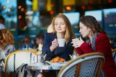 Deux jeunes filles en café extérieur parisien Image stock