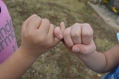 Deux jeunes filles fermant à clef les doigts rosâtres - meilleurs amis Photographie stock