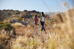 Deux jeunes filles flânant vers le haut du flanc de coteau Photo stock