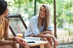 Deux jeunes filles gaies s'asseyant au caf? dehors images stock