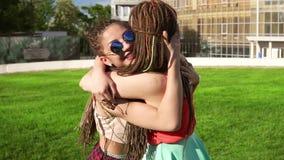 Deux jeunes filles heureuses avec redoute de s'étreindre Amis féminins enthousiastes s'embrassant et riant pendant clips vidéos