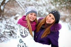 Deux jeunes filles heureuses ayant l'amusement dans le stationnement de l'hiver à l'extérieur Image stock
