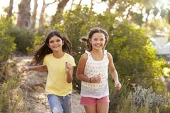 Deux jeunes filles heureuses courant dans une forêt, se ferment  Photo libre de droits
