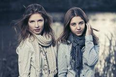 Deux jeunes filles heureuses de mode marchant par le lac Photo stock