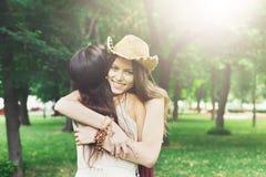 Deux jeunes filles heureuses s'étreignent en parc d'été Image libre de droits
