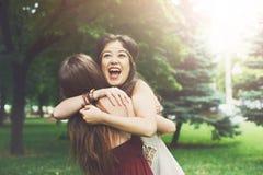 Deux jeunes filles heureuses s'étreignent en parc d'été Photo stock