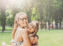 Deux jeunes filles heureuses s'étreignent en parc d'été Photos libres de droits
