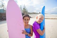 Deux jeunes filles heureuses tenant des planches de surf à la plage Photos libres de droits