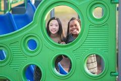 Deux jeunes filles jouant ensemble au terrain de jeu d'école Photographie stock libre de droits