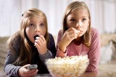 Deux jeunes filles mangent le maïs éclaté et la montre TV Photos libres de droits