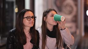Deux jeunes filles marchent par la vieille ville la nuit et la causerie, boivent du café chaud banque de vidéos