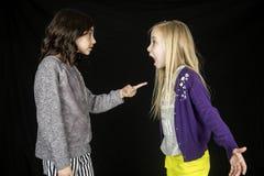 Deux jeunes filles mignonnes discutant une fille dirigeant le doigt Photographie stock libre de droits