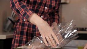 Deux jeunes filles ont mis le poulet dans un sac de cuisson Dîner délicieux de poulet banque de vidéos