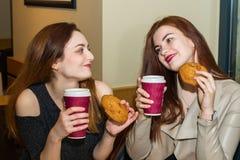Deux jeunes filles parlant dans un cafétéria Photographie stock