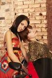 Deux jeunes filles posant sur une moto rouge Images stock