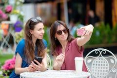 Deux jeunes filles prenant le selfie avec le téléphone intelligent au café d'extérieur Deux femmes après l'achat avec des sacs se Photos libres de droits