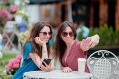 Deux jeunes filles prenant le selfie avec le téléphone intelligent au café d'extérieur Deux femmes après l'achat avec des sacs se Image stock