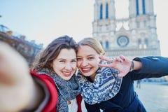 Deux jeunes filles prenant le selfie près de Notre-Dame à Paris Images stock