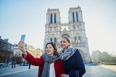 Deux jeunes filles prenant le selfie près de Notre-Dame à Paris Photographie stock