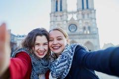 Deux jeunes filles prenant le selfie près de Notre-Dame à Paris Photographie stock libre de droits