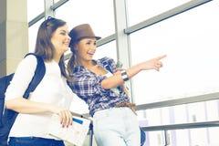 Deux jeunes filles regardent la carte et montrent la direction de l'index Image libre de droits