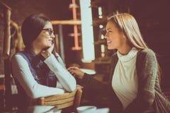 Deux jeunes filles s'asseyant en café et ayant la conversation Photo stock
