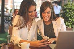 Deux jeunes filles s'asseyant en café utilisant le téléphone intelligent Apparence de fille photographie stock