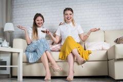 Deux jeunes filles s'asseyent sur le divan Photographie stock