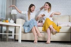 Deux jeunes filles s'asseyent sur le divan Photo stock