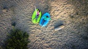 Deux jeunes filles se couchent sur la plage sablonneuse Image libre de droits